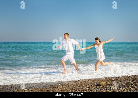 Happy young couple runs having joined hands on the sea coast. The guy and girl dressed in easy white clothes. On - Stock Photo