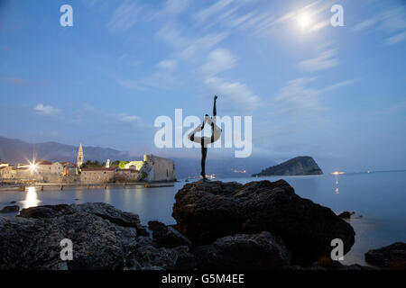 Full moon over the dancing woman statue and old town of Budva city, Montenegro - Stock Photo