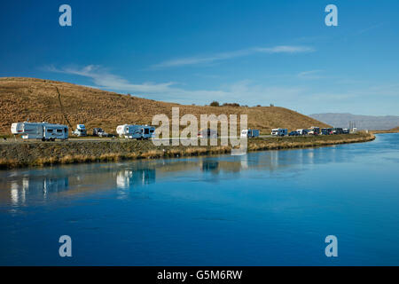 People fishing, caravans and campervans by Lake Ruataniwha, near Twizel, Mackenzie District, South Canterbury, New - Stock Photo