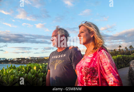 Golden light on tourists enjoying coastal walkway in Wailea, Maui, at sunset - Stock Photo