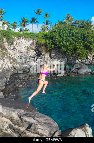 Woman jumps off cliff in Kapalua, Maui - Stock Photo