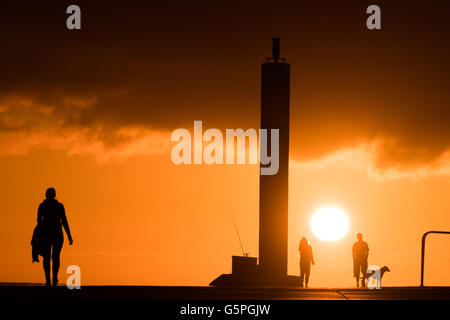 Aberystwyth Wales UK, Wednesday 22 June 2016 UK weather, People walking along the harbour pier at sunset in Aberystwyth - Stock Photo
