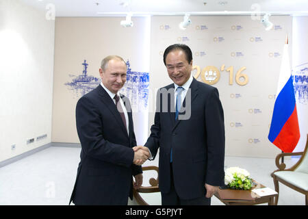 St.Petersburg. 17th June, 2016. President of Xinhua News Agency Cai Mingzhao (R) shakes hands with Russian President - Stock Photo