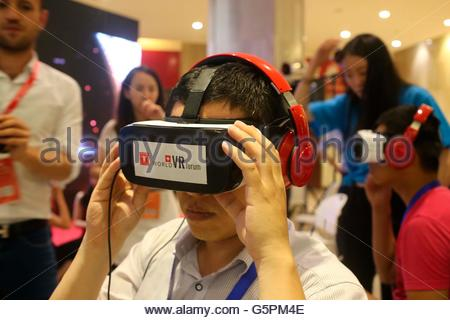 Beijing, China. 23rd June, 2016. People experience VR virtual reality terminal products at the 15th China Internet - Stock Photo