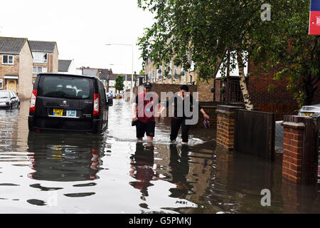 London, UK. 23rd June 2016. UK Weather: Couple seen wading through the flooded road following heavy rain in East - Stock Photo