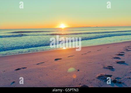 Retro effect coastal wide image lens flare leading to footprints on sand from sea and horizon at  sunrise - Stock Photo