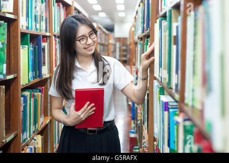 Asian student in uniform reading in the library at university - Stock Photo