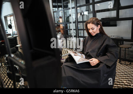 Beautiful young woman sitting in beauty salon and reading fashion magazine - Stock Photo