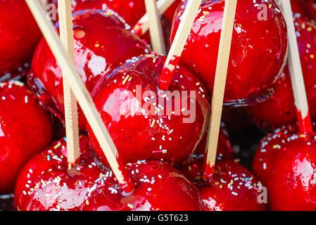 Sweet glazed red toffee candy apples on sticks for sale on farmer market or country fair. Stock Photo