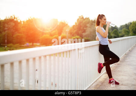 Woman drinking water after running session - Stock Photo