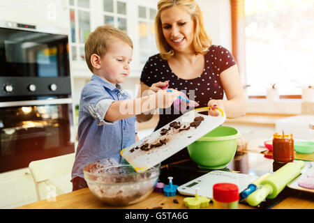 Beautiful child and mother baking in kitchen with love - Stock Photo