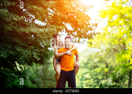 Man carrying woman piggyback after jogging is done - Stock Photo