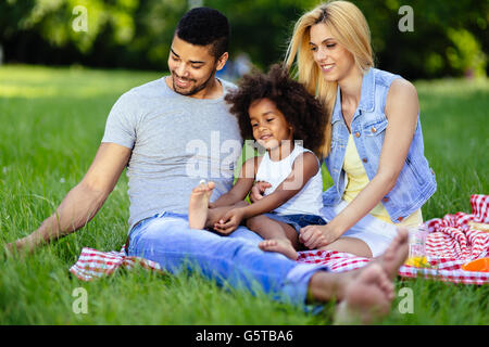 Family picnicking outdoors with their cute daughter - Stock Photo