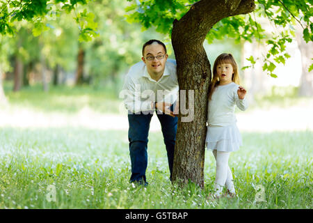 Down syndrome siblings  playing outdoors - Stock Photo