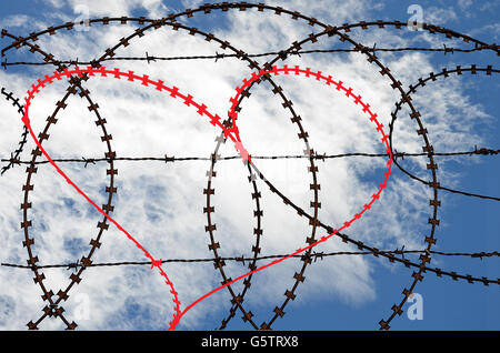 Natural heart shape (digitally coloured red) in a barb wire fence on sky background. Love, freedom, peace and compassion - Stock Photo