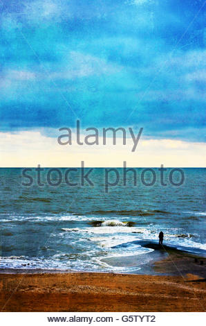 a young woman waiting for the storm on the beach - Stock Photo