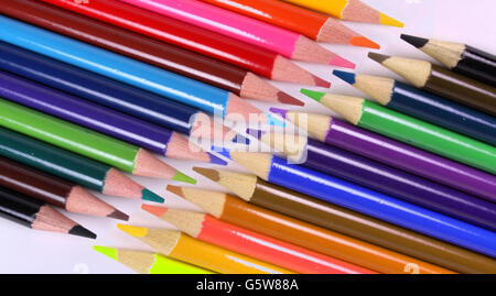 A set of colorful pencils facing each other, on a white sheet. - Stock Photo