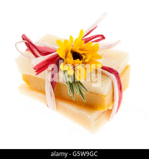 Several herbal handmade artisan soap pieces tied with fresh flowers isolated on white background - Stock Photo