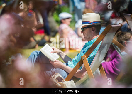 People reading books in the warm summer sunshine at The Hay Festival of Literature and the Arts, Hay on Wye, Powys, - Stock Photo