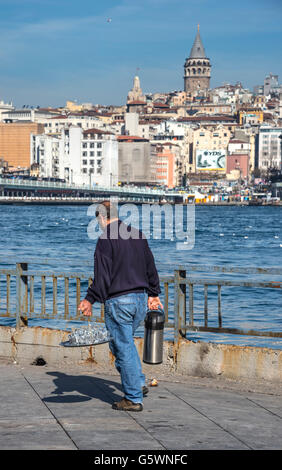 Tea vendor at Eminonu with view across the Golden Horn and the Galata tower in the background. Istanbul, Turkey. - Stock Photo