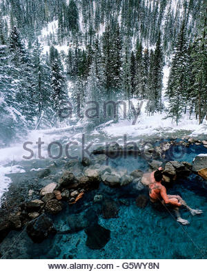 Forest in winter, man sitting in a hot spring. Snow on trees and on ground. - Stock Photo