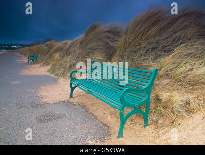 Green seats in sand dunes on a stormy day. - Stock Photo