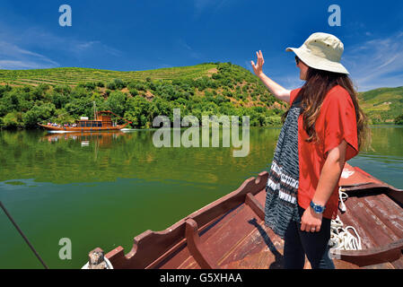 Portugal: Girl with hat in traditional Rabelo boat greeting other boat on river Douro Tour - Stock Photo