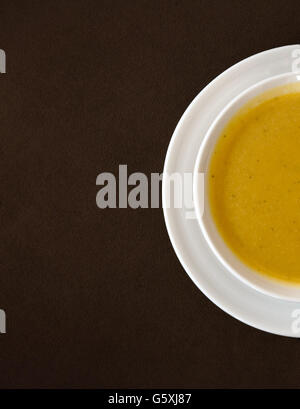 Top view of soup served in a white bowl and plate - Stock Photo