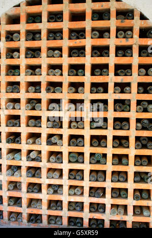 vintage wine bottles stacked in the wine cellar - Stock Photo