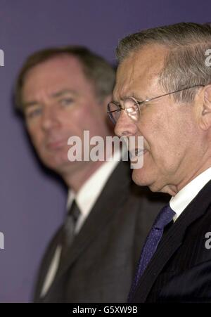 The United States Secretary of Defence Donald Rumsfeld (right) answers a question from a journalist, during a joint press conference with Minister of Defence Geoff Hoon (left), in Whitehall. Stock Photo
