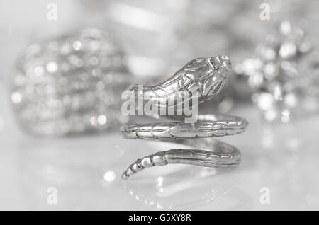 Silver ring in the shape of a snake and other jewelry. - Stock Photo