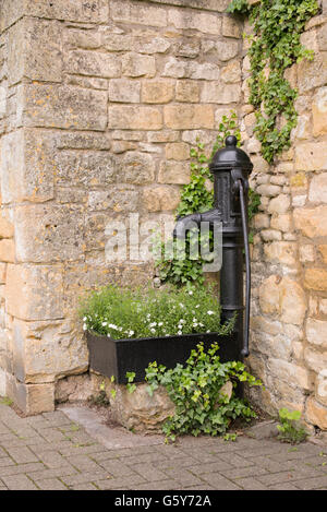 Old cast iron hand water pump and trough with flowers on the street in in Chipping Campden, Gloucestershire, England