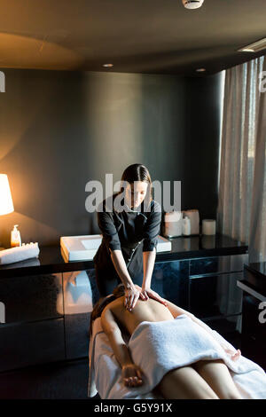 Beautiful young and healthy woman having her shoulder and body massaged by a professional masseur at a spa center - Stock Photo
