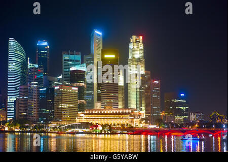Singapore Downtown Core reflected in a river at night - Stock Photo