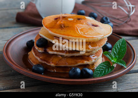 Blueberry pancakes on a plate pour maple syrup - Stock Photo