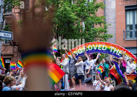 NEW YORK CITY - JUNE 28, 2015: Celebrants at the annual gay pride parade wave rainbow flags as they pass in front - Stock Photo