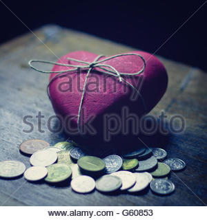 Red heart with coins - Stock Photo