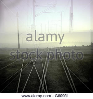 View from a train of horizon and train tracks overlapping in sunset - Stock Photo