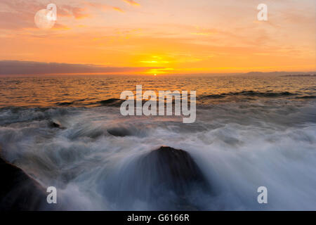Ocean sunset is a brightly lit golden seascape with a gentle wave rolling to the shore. - Stock Photo