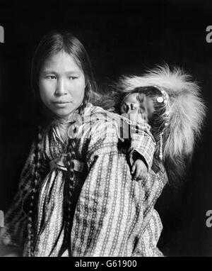 Inuit woman, wearing traditional clothes, with a papoose on her back in Arctic Alaska. Photo by H G Kaiser, c.1912