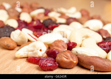 Close bokeh shot of an assortment of nuts dried fruit laid out on a wooden table - Stock Photo