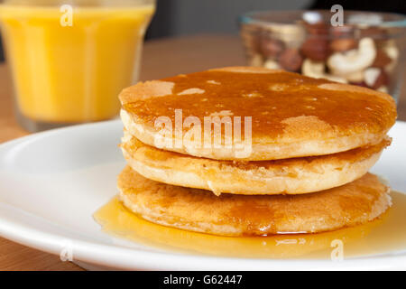 Close up shot of a stack of fresh golden pancakes on a plate covered in rich maple syrup aside a glass of fresh - Stock Photo