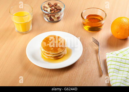 Plate of syrup covered pancakes with a bowl of mixed nuts and dried fruit on a breakfast table with a glass of fresh - Stock Photo
