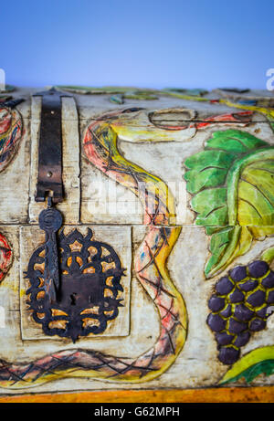 A charming & whimsical folk art style wood carved trunk depicting snakes and grapes and birds with decorative metal - Stock Photo