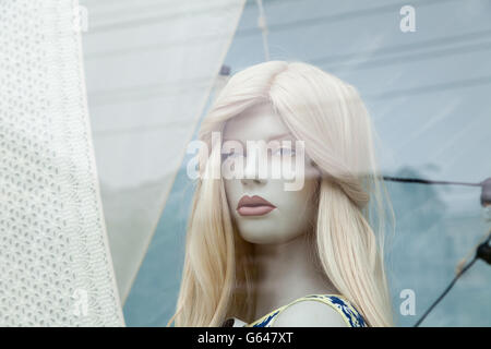 Cute realistic female mannequin face close-up in a shop window. Beautiful Caucasian manikin head with blonde hair - Stock Photo