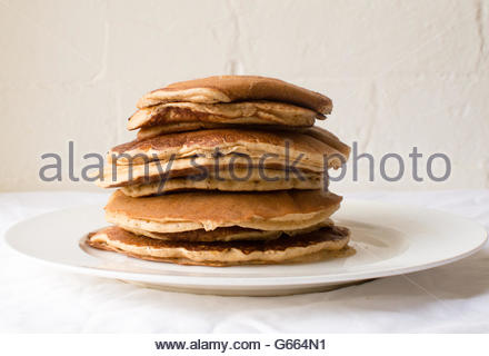 Stack of spelt flour pancakes on white plate on white tablecloth against white brick wall - Stock Photo