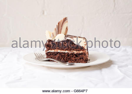 Slice of chocolate cake on white plate with metal fork, on white tablecloth against rustic white brick wall - Stock Photo