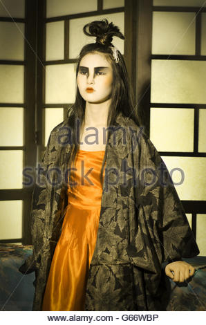 Beautiful young Japanese woman wearing orange dress and kimono. - Stock Photo
