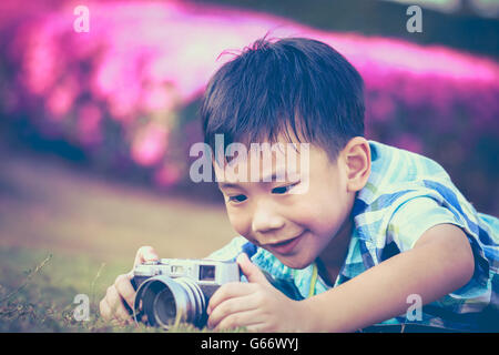 Asian boy taking photo by vintage film camera on blurred nature background at the day time. Vintage picture style. - Stock Photo
