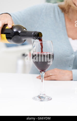 Close Up Of Woman Pouring Large Glass Of Red Wine - Stock Photo